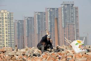 Waste collector scavenging metals from torn-down houses in Shenyang, China.