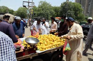 Vendor sells mangoes on his pushcart at a roadside in Karachi.