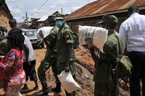 Soldiers delivering maize flour to needy people in a Kampala suburb.