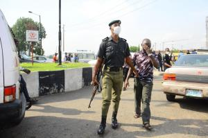 Nigerian police officer arresting man for disobeying lockdown.