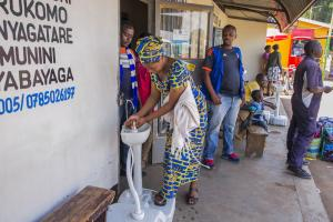 A woman washing her hands before entering a bus ticket office in Kigali, Rwanda.
