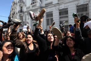 Tunisian protesters hold up their shoes in a gesture of contempt for Sihem Badi, the minister for women's affairs.