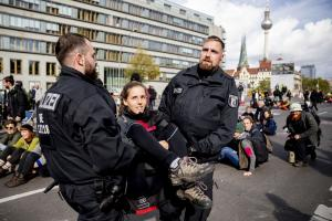 Police officers carrying an XR protester away from a bridge in Berlin.