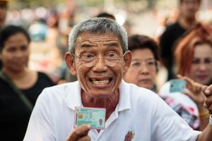 Unable to cast their votes, angry citizens display identity cards in Bangkok.
