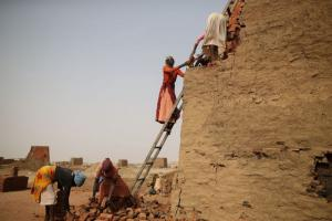 Personnel from the International Criminal Court are not allowed to collect evidence in Sudan. Refugee women work in a brickyard in the conflict region of Darfur.