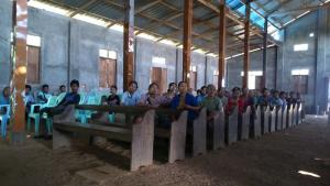 Members of local self-help groups in the Irrawaddy Delta in Myanmar gather in their church to discuss how they can improve their incomes by communal pig farming.