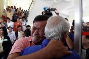Surviving Khmer-Rouge victims embrace after the announcement of the verdicts.