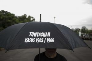 "Making a statement in Jakarta: the writing on the umbrella means: ""Resolve the 1965/1966 case."""