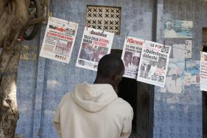 Young man reading headlines at a news stand in Dakar in 2009.