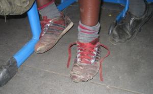 Attending school helps children from poor families escape poverty: footwear seen in a Nairobi classroom.