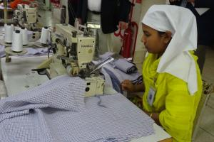Workers in the formal sector often enjoy health insurance and pension plans: a seamstress in Bangladesh.