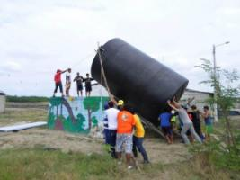 Installing a village's new water tank.