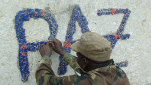 "Guinean soldier decorating the ""peace fountain"" to commemorate the casualties of civil strife in Bissau, the capital city."