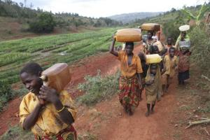 Extreme poor people like here in Burundi often have to walk many kilometres to fetch drinking water. This is work for women and children.
