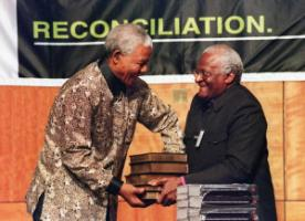 Nelson Mandela receives the five volumes of South Africa's Truth and Reconciliation Commission final report from its chairperson Archbishop Desmond Tutu in 1998