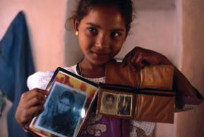 A girl showing photos of her mother who died in child birth.