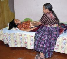 A traditional midwife in Guatemala examines a pregnant woman.