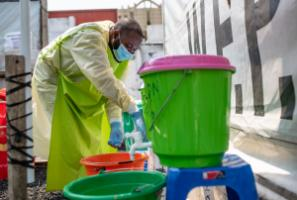 IRC staff member taking off his personal protective equipment during Ebola outbreak in Goma in 2019.