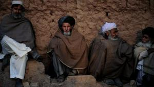 Afghan refugees sit outside their homes in Islamabad.