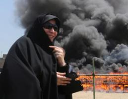 An Iranian woman watches confiscated drugs being burned in Tehran in 2013.