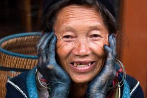 Woman of the Hmong ethnic group in Vietnam, her hands black from using dye. Hmong villages are a popular destination for Chinese tourists.