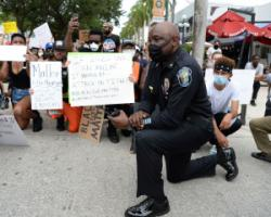 Police officer taking a knee with Californian anti-racism activists.