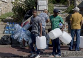 Collecting water from a public spring in a suburb of Cape Town.