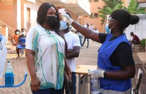 The pandemic is slowing down economic life: taking a person's temperature in Accra, Ghana.