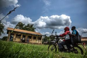 A Kenyan health worker delivers vaccines in a cool box on a motorcycle.