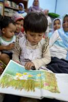 Toddler with a picture book in Aceh.