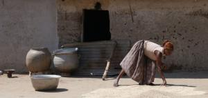 Woman drying grain in Ghana's Upper West Region.