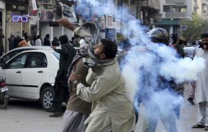 A fanatic tossing a tear-gas canister towards police during anti-Asia-Bibi protests in Karachi in February 2019.