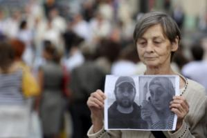 A demonstrator in Moscow with photos of killed human rights activists from Chechnya.