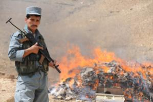 """""""The more it was tried to put an end to the opium economy, the more violent mafia structures emerged."""" An Afghan policeman in front of a bonfire of  confiscated drugs"""