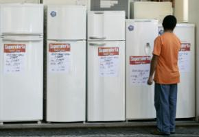 """The social policies of President Lula da Silva's administration sustained demand by stimulating consumption."" A man checking out refrigerators at a store in Rio"