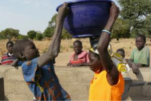 An unusual scene: a boy ! helping a girl to lift a 20-litre water container
