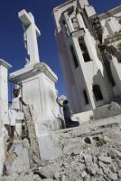 A woman prays in the cathedral ruins in Port-au-Prince