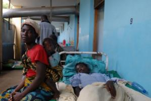 Aid withdrawal is compounding health care problems in Malawi – a patient with visiting family members in a hospital in 2007