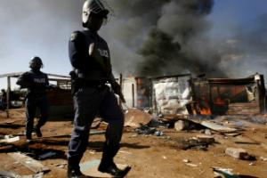 A policeman walks past a burning shack after xenophobia attacks in a Johannesburg squatter camp in May this year