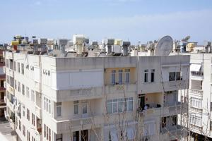 Water tanks, solar panels and satellite dishes on a roof in Alanya, Turkey