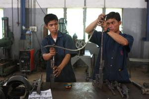 """Income and employment smooth the way back into civilian life"": After disarmament in Cambodia, young adults learn how to make chairs, benches and tables out of machine guns"