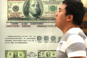 The USA and China have been at odds over exchange rates for a decade: a 100 dollar bill shown in the window  of a bank in Beijing