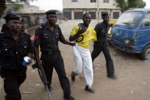 SA man is detained by police officers on the outskirts of Kano during election-related unrest in 2007