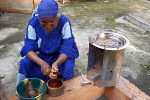 A Nigerian woman using an energy-efficient wood stove
