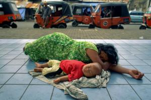 Mother sleeping on a sidewalk in Jakarta