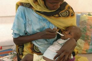 Mother feeding her child in a refugee camp in Southern Sudan