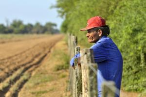 Indigenous Argentine at a fence that denies his people acces to traditional homelands