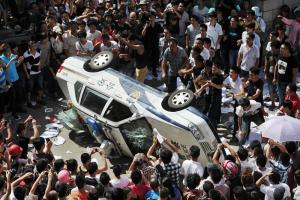 Protestors toppling a police car in Qidong in July